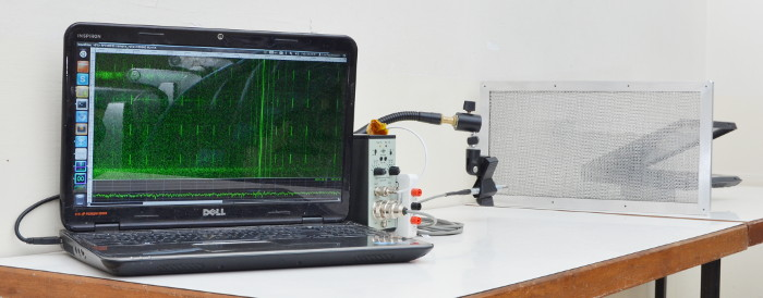 microphone measuring a laptop through a mesh ventilation panel